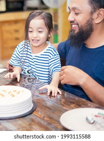 Happy toddler with father cutting the brithday cake at home.