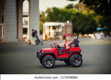 Happy toddler girl drivind big red toy sport car, having fun, riding away. Resting on holidays in park outdoor