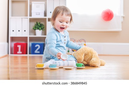 Happy toddler girl have tea with her teddy bear