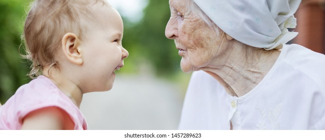 Happy toddler girl and her great grandmother looking at one another, laughing and talking outdoors