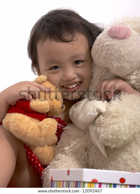 happy toddler girl with her teddy bears