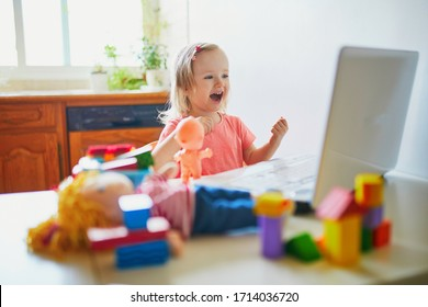 Happy toddler girl with laptop and toys. Kid using computer to communicate with friends, elderly relatives or kindergartners. Education or online communication for kids. Stay at home entertainment