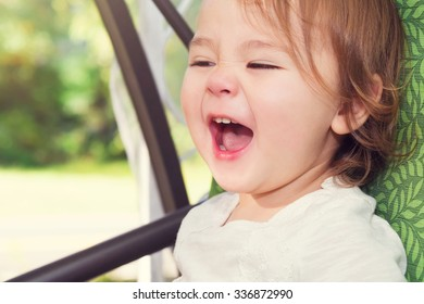 Happy toddler girl laughing while on a swing outside