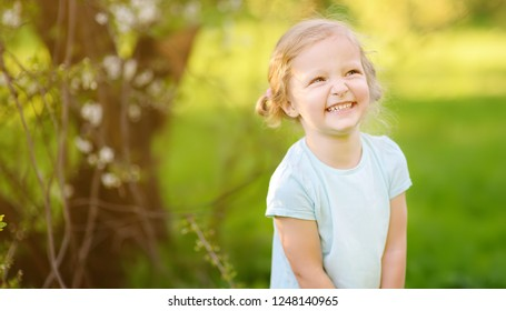 Happy toddler girl outdoors portrait in summer day. Smiling and charming child. Little lady with blonde and curly hair