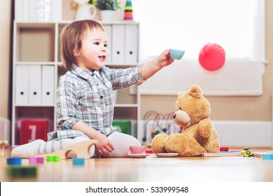 Happy toddler girl playing with her teddy bear at home