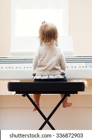 Happy toddler girl playing the piano from behind