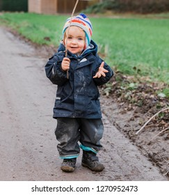 Happy toddler girl playing with a stick – Kempen, Germany