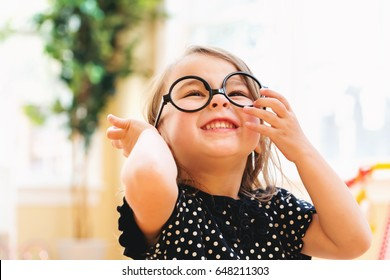 Happy toddler girl playing with sunglasses