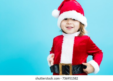 Happy toddler girl in a Santa costume on a blue background