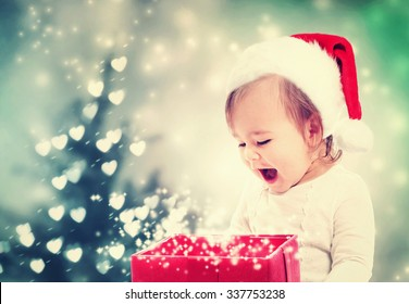 Happy Toddler girl with a Santa hat looking at Christmas present box
