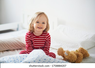Happy toddler girl in striped red and white pajamas sitting on bed right after awaking. Day naps for small kids