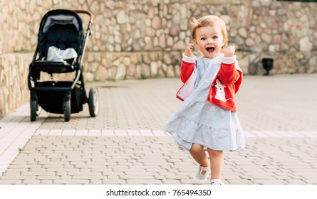 Happy toddler girl walking with stroller behind her