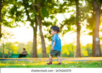 Happy toddler little boy first running on green grass field sunset light in city park outdoor