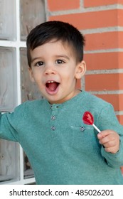 Happy toddler on the street eating a lollipop