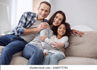 Happy together. Beautiful content curly-haired girl smiling and sitting on the couch with her parents and they hugging each other