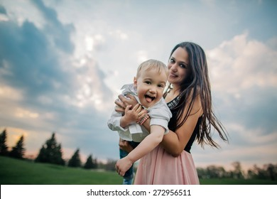 Happy together. Beautiful young mother and her son having fun at cloudy field. Wide angle photo