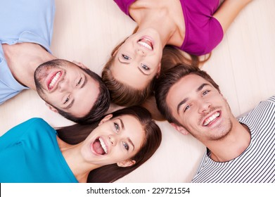 Happy together. Cheerful friends lying down and looking at camera