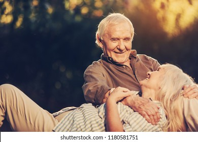 Happy together. Cheerful laughing elderly lady lying on male knees and turning sight up at him. Copy space on left side