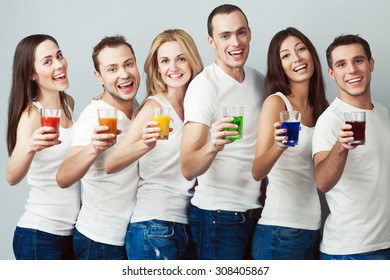 Happy together concept. Company of healthy boys and girls in white t-shirts, sleeveless shirts and blue jeans standing with vegetable, fruit juice posing over gray background. Urban style. Studio shot