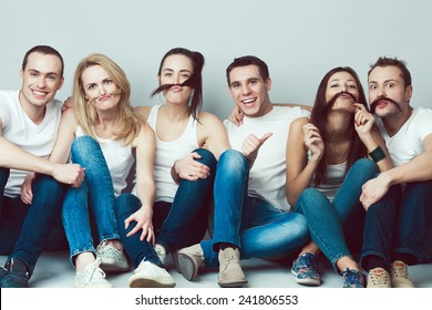 Happy together concept. Group portrait of healthy boys and girls in white t-shirts, sleeveless shirts and blue jeans sitting and posing over gray background. Copy-space. Urban style. Studio shot