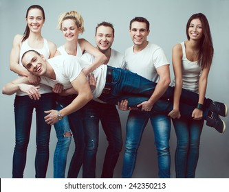 Happy together concept. Group portrait of healthy boys and girls in white t-shirts, sleeveless shirts and blue jeans holding friend in hands and posing over gray background. Urban style. Studio shot