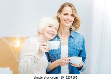 Happy together. Happy emotional senior woman leaning her head to the young kind granddaughter and smiling while holding a cup of tea and standing next to the window