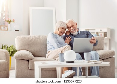 Happy together. Nice beaming couple spending weekend at home while watching video on the laptop