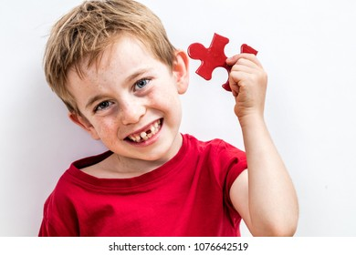 happy toothless child with freckles finding a piece of jigsaw for concept of fun success, growing up idea or solution to child healthcare, white background