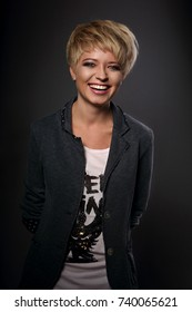Happy toothy laughing young blond woman with short bob hair style looking in grey trendy jacket on dark background.