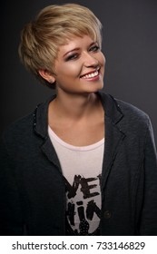 Happy toothy smiling young blond woman with short bob hair style looking in grey trendy jacket on dark background. Closeup portrait