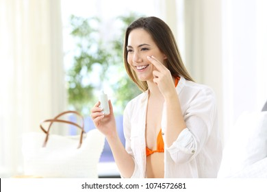 Happy tourist applying sunscreen protection in an hotel room on summer vacations on the beach