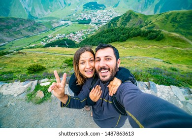 happy tourist backpackers couple taking selfie photo in Stepantsminda also called Kazbegi, Georgia in the Caucasus Mountains