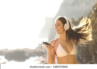 Happy tourist in bikini listening to music and dancing on summer vacation on the beach