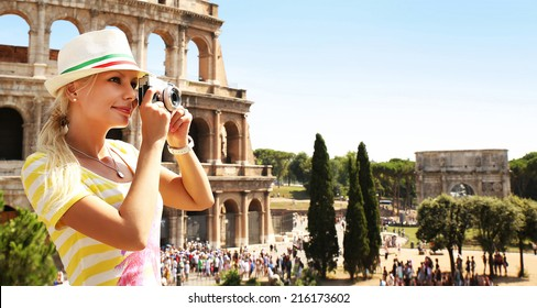 Happy Tourist and Coliseum, Rome. Cheerful Young Blonde Woman with Camera in Italy. Travel in Europe