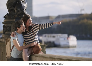 Happy tourist couple in love pointing at view on vacation
