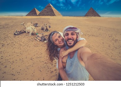 happy tourist couple on camel in Giza. holiday travel tpur near Pyramid of Khafre, Egypt