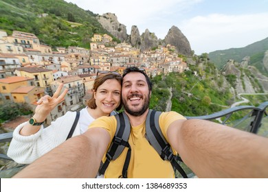 happy tourist couple taking selfie in castelmezzano town, in the Dolomiti lucane, basilicata region, Italy