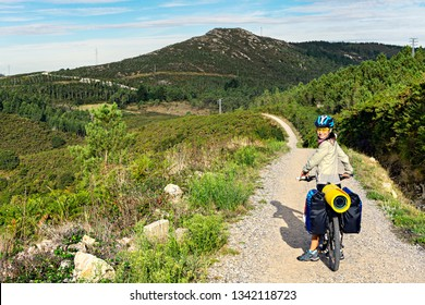 Happy tourist cyclist on stony hilly road. Spain. Europe.