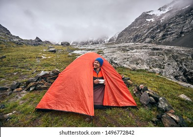 Happy tourist is eating his breakfast at orange tent in the foggy mountains at rainy morning in Karakol national park, Kyrgyzstan