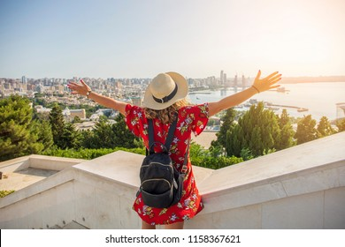 Happy tourist girl on the observation deck on panorama of Baku city bakcground.