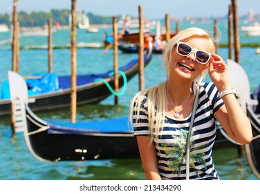 Happy Tourist and Gondolas in Venice, Italy. Cheerful Young Blonde Woman with Sunglasses. Travel in Europe