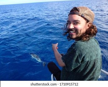 Happy tourist having fun on a whale watching tour, with dolphins swimming and playing under the sailboat, in Mallorca, a balearic island, Spain. Could be Azores, Greek or Italian trip.