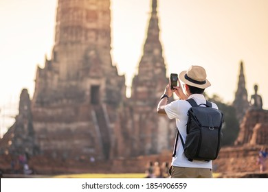 Happy tourist man with backpack Taking Photo by mobile smartphone, during visiting in Wat Chaiwatthanaram temple in Ayutthaya Historical Park, summer, solo, Asia and Thailand travel concept