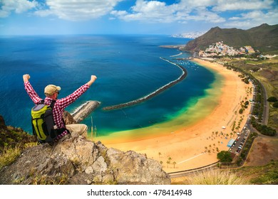 happy tourist man sitting on the edge of a cliff with outstanding overview of Playa de Las Teresitas, Canary Islands, Spain