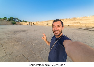 happy tourist man taking selfie photo in front of the old wall of the city of Fez, Morocco. Fez has the largest medina old city of the world