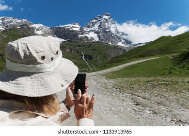 Happy tourist on a mountain landscape at Matterhorn in italian Alps.