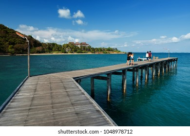 Happy tourist people selfie at Wooden plank pier bridge with seascape and clear blue sky at Khao Laem Ya in Mu Ko Samet National Park, Rayong Province, Thailand