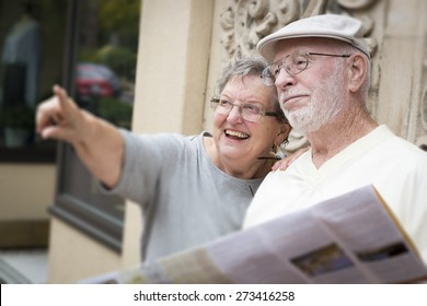 Happy Tourist Senior Couple Looking at Brochure Map.