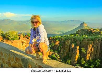 Happy tourist sitting on the rocks after hiking at Valley of Desolation near Graaff-Reinet, South Africa.Sunset light. Blonde woman enjoying aerial views of Camdeboo National Park, Karoo, Eastern Cape