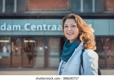 Happy tourist standing at the central Amsterdam railway station